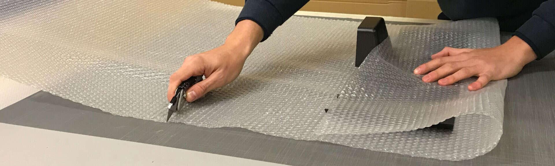 Worker Cutting Bubble Wrap