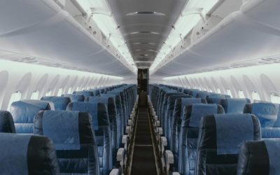 View down isle of airplane with blue seats